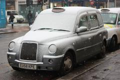 London Taxi covered in snow - stock photo