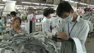 Stock Video Footage of Textile Clothing Factory: Medium shot supervisors with clipboard and worker