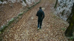 AERIAL: Young man jogging in frozen forest Stock Footage