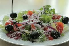 Pouring balsamic sauce onto vegetable salad, close up NTSC Stock Footage