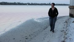 Depressed woman walking along the shore Stock Footage