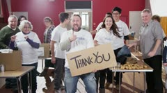 "Group of charity volunteers give thumbs up to camera with a ""Thank You"" sign Stock Footage"