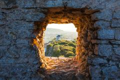 Old windmill through window in fortress wall Stock Photos