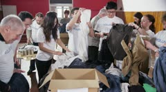 Charity volunteers in white printed t. shirts sorting through donated clothing Stock Footage