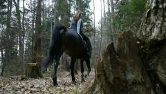 DOLLY: Girl horseback riding in woods - stock footage