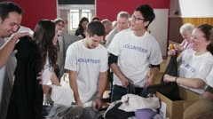 Charity volunteers have fun together as they sort through donated goods Stock Footage