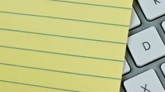 Lined pad of paper and a computer keyboard Stock Footage