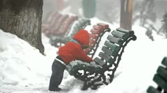 Little baby cleaning a bench in a winter park and looking to the camera Stock Footage