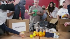 Charity volunteers and community members sorting through donated goods Stock Footage