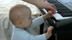 Mother hands playing on piano and baby touching the piano Stock Footage