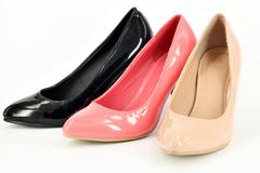 Ocher pink and black women shoes on white Stock Photos