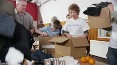 Charity volunteers and community members sort through donated food and clothing - stock footage