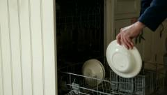 Man puts plates into dishwasher Stock Footage