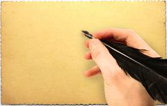 hand writing with quill on old grungy postcard - stock photo