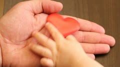 Baby hand taking off the red heart from his parent hand Stock Footage