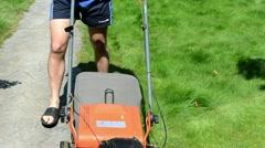 Gardener man shorts flip-flop shoes mower cut grass stone path Stock Footage