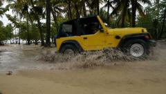 Driving through a puddle with yellow jeep - stock footage