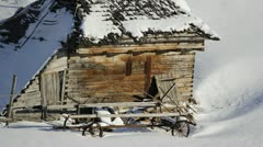 Isolated rustic wooden house, wooden cart wheels and intact snow Stock Footage