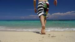 Young man running into the caribbean sea Stock Footage