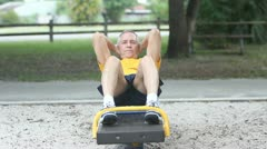 Senior healthy man doing sit-ups in park Stock Footage