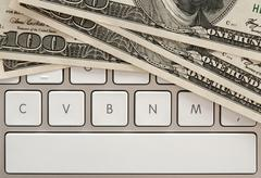 Money bills on computer keyboard with spacebar Stock Photos