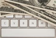 Money bills on computer keyboard with spacebar Stock Photos