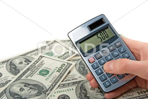 Stock photo of Money and hand holing a calculator