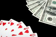 Playing cards and money on black background Stock Photos