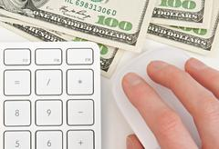 Money, keyboard and hand on computer mouse - stock photo