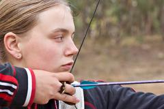 teenage girl doing archery - stock photo