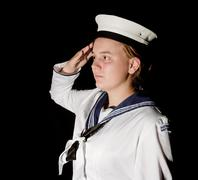 navy seaman saluting on black - stock photo