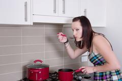 Young woman cooking in kitchen Stock Photos