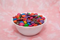 bowl of smarties on pink background - stock photo