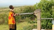 Masai Woman Pumping Water Stock Footage