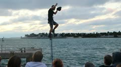 Juggler on unicycle does hat trick off one foot Stock Footage