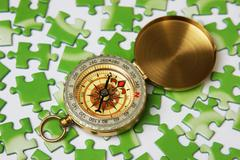 Compass on the green puzzle Stock Photos