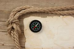 vintage paper with compass and rope on old wooden boards - stock photo