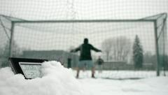 Determined soccer players in winter time thermometer in foreground Stock Footage
