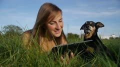 Girl with dog using a digital tablet Stock Footage