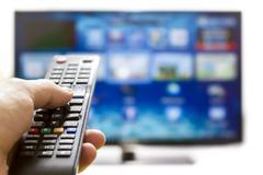 Smart TV ja käsi painamalla kauko-ohjaimen Kuvituskuvat