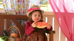Little girl sits on a veranda and eats  water-melon Stock Footage