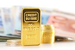 50 gram gold bar, banknotes and coins - stock photo