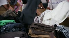 Charity volunteers in printed t. shirts sort through piles of donated clothing - stock footage