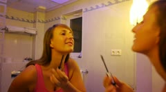 Young woman applying makeup in the mirror Stock Footage