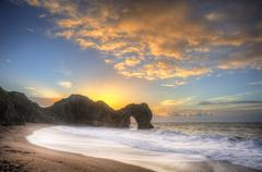 Vibrant sunrise over ocean with rock stack in foreground Stock Photos