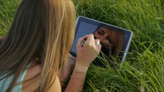 Young woman with tablet in a meadow Stock Footage