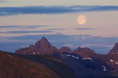 Stock Photo of moon above rocky peaks