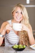 young beautiful woman enjoying healthy breakfast in the kitchen - stock photo