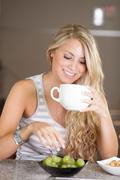 young beautiful woman enjoying healthy breakfast in the kitchen - stock photo