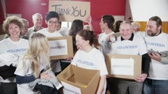 "Happy group of fundraisers holding donated goods and a ""Thank You"" sign Stock Footage"